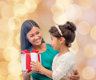 Happy mother and child girl with gift box. Christmas, holidays, celebration, family and people concept - happy mother and child girl with gift box over beige Stock Photos