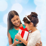 Happy mother and child girl with gift box Stock Photos
