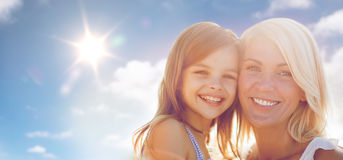Happy mother and child girl over sun in blue sky Stock Photo