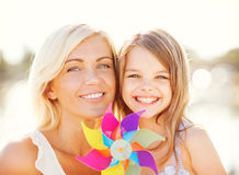 Happy mother and child girl with pinwheel toy Royalty Free Stock Images