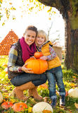 Happy mother and child holding pumpkin. Portrait of happy mother and child holding pumpkin Royalty Free Stock Photo
