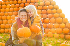 Happy mother and child holding pumpkins. Portrait of happy mother and child holding pumpkins Stock Photography