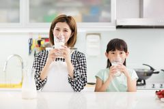 Mother and child in kitchen drinking milk royalty free stock photos