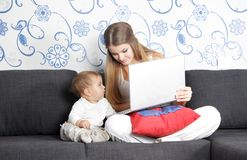 Happy mother and child with laptop at home Royalty Free Stock Image
