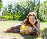 Happy mother and child. Laying on grass in yard Royalty Free Stock Image