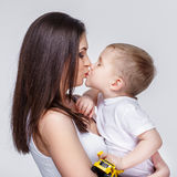 Happy mother with a child on light grey background Royalty Free Stock Image