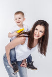 Happy mother with a child on light grey background Royalty Free Stock Photos