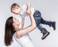 Happy mother with a child on light grey background Stock Photos