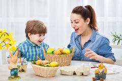 Happy mother and child looking at easter colored eggs and smilin Royalty Free Stock Photos