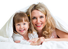 Happy mother and child lying under the blanket Stock Photo