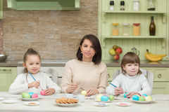 Happy mother and child paint Easter eggs on the kitchen table Royalty Free Stock Photography