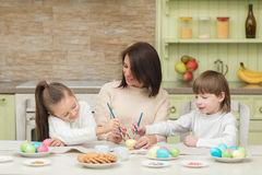 Happy mother and child paint Easter eggs on the kitchen table Stock Images