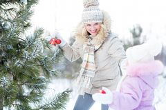 Happy mother and child playing with christmas tree Royalty Free Stock Images