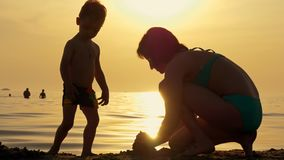 Happy Mother and child playing with sand on the beach against sunset.