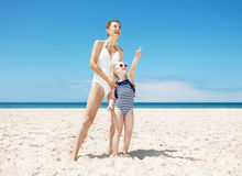 Happy mother and child pointing to somewhere at sandy beach. Family fun on white sand. Full length portraits of happy mother and child pointing to somewhere Stock Photos
