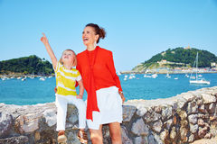 Happy mother and child pointing up in front of lagoon Stock Photography