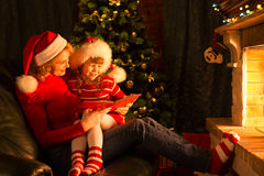 Happy mother and child reading book in christmas Stock Photo