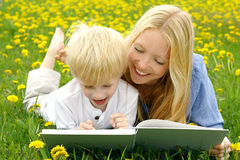 Happy Mother and Child Reading Book Outside in Meadow stock images