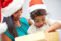 Happy mother and child in santa hats with gift box Royalty Free Stock Photography
