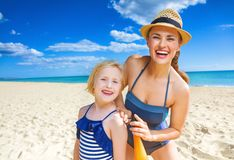 Happy mother and child on seashore applying suntan lotion. Sun kissed beauty. happy healthy mother and child in swimwear on the seashore applying suntan lotion Stock Images