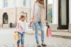 Happy mother and child with shopping bags in city Royalty Free Stock Photo