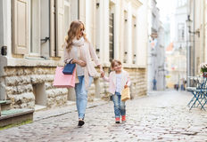 Happy mother and child with shopping bags in city. Sale, consumerism and people concept - happy mother and child with shopping bags walking along city street royalty free stock photos