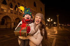 Happy mother and child showing Christmas gift box in Venice Stock Images