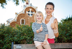 Happy mother and child showing thumbs up in Park Guell Stock Image