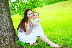 Happy mother and child sitting on the grass under tree in summer Royalty Free Stock Images