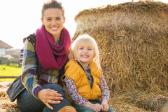 Happy mother and child sitting on haystack Stock Photos
