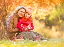 Happy mother and child sitting outdoor in autumn royalty free stock photo