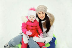 Happy mother and child sitting together on sled in winter da Royalty Free Stock Photos
