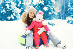 Happy mother and child sitting together on sled in winter day Stock Photo