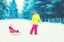 Happy mother and child on sled in winter. Snowy day Royalty Free Stock Photo