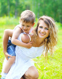 Happy mother with child son having fun outdoors in summer Stock Images