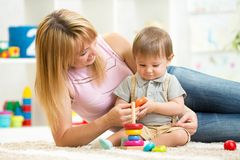 Happy mother and child son play together indoor at Stock Images