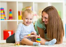 Happy mother and child son play together indoor at. Happy mother and child son playing together indoor at home Royalty Free Stock Photography