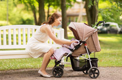 Happy mother with child in stroller at summer park Royalty Free Stock Image