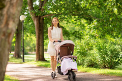 Happy mother with child in stroller at summer park Royalty Free Stock Photography
