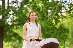 Happy mother with child in stroller at summer park Stock Photography