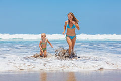 Happy mother with child swim with fun in sea surf. Happy family - mother and small baby daughter swim with fun in sea surf and run with splashes to black sand Stock Photo