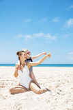 Happy mother and child in swimsuits at beach pointing aside Stock Photos