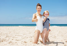 Happy mother and child in swimsuits at beach showing thumbs up Royalty Free Stock Photography