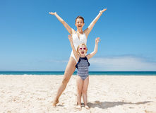 Happy mother and child in swimsuits at sandy beach rejoicing Royalty Free Stock Photos