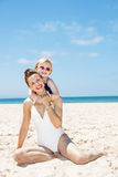 Happy mother and child in swimsuits at sandy beach on sunny day. Family fun on white sand. Portrait of happy mother and child in swimsuits at sandy beach on a stock image