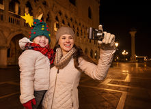 Happy mother and child taking photos on Piazza San Marco, Venice Royalty Free Stock Photo