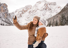 Happy mother and child taking photos in winter outdoors Royalty Free Stock Photography