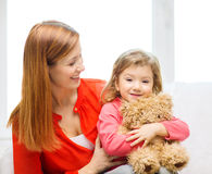 Happy mother and child with teddy bear at home Royalty Free Stock Photos