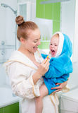 Happy mother and child teeth brushing and tongue cleaning Stock Photos