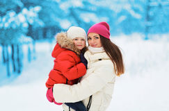 Happy mother and child together in snowy day Royalty Free Stock Images